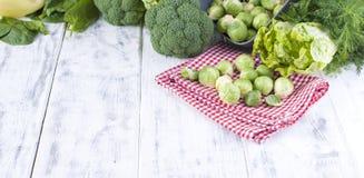Различные свежие зеленые овощи, ростки Брюсселя и овощи На белой деревянной предпосылке место текста сочинительства Стоковые Изображения