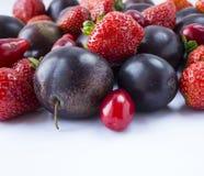 Различные свежие плодоовощи лета Зрелые клубники и сливы на белой предпосылке Свежие фрукты на границе изображения с космосом экз Стоковое Фото