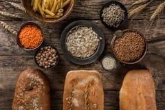 Различные свежий хлеб и хлопья на деревенской деревянной предпосылке Творческий план сделанный из хлеба Здоровая концепция еды, в стоковая фотография
