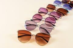 Различные стильные солнечные очки на желтой предпосылке Картина Предпосылка солнечных очков Оптический магазин стоковое изображение