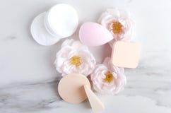 Различные типы косметических губок, пусковых площадок хлопка и цветков на белой мраморной поверхности стоковая фотография