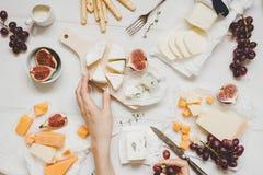 Различные типы сыра с плодоовощами и закусками на деревянной белой таблице Взгляд сверху Стоковое Изображение