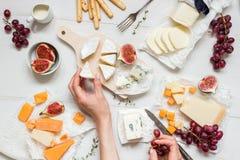 Различные типы сыра с плодоовощами и закусками на деревянной белой таблице Взгляд сверху Стоковая Фотография