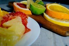Различные цитрусовые фрукты отрезали в куски апельсин, лимон, известку, грейпфрут, помело Распространите вне на деревянной доске  стоковые фотографии rf