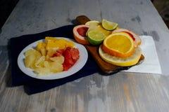Различные цитрусовые фрукты отрезали в куски апельсин, лимон, известку, грейпфрут, помело Распространенный вне на деревянной доск стоковое фото rf