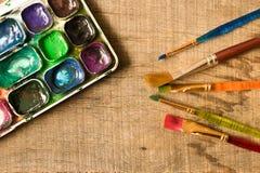 Различные щетки и комплект красок на старом деревянном столе _ Стоковое Изображение
