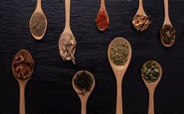 Различный вид высушенных листьев, плодоовощ и цветка положил в много вид деревянных ложек на черную предпосылку с космосом экземп Стоковая Фотография