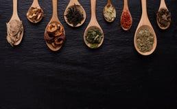 Различный вид высушенных листьев, плодоовощ и цветка положил в много вид деревянных ложек на черную предпосылку с космосом экземп Стоковое Изображение RF
