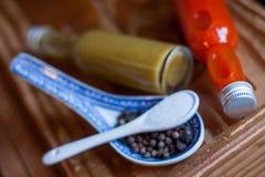 2 различных горячих соусы, соль и перца стоковые фото