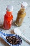2 различных горячих соусы, соль и перца стоковая фотография