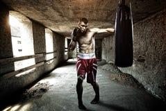 Разминка бокса молодого человека в старом здании стоковое фото rf