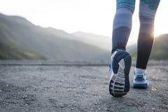 разминка женщины здоровья восхода солнца идущего ботинка бегунка дороги jog пригодности ног принципиальной схемы крупного плана Стоковые Фото