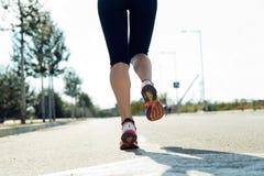 разминка женщины здоровья восхода солнца идущего ботинка бегунка дороги jog пригодности ног принципиальной схемы крупного плана Стоковая Фотография