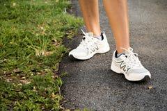 разминка женщины здоровья восхода солнца идущего ботинка бегунка дороги jog пригодности ног принципиальной схемы крупного плана Стоковые Изображения RF