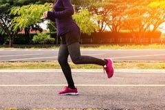 разминка женщины здоровья восхода солнца идущего ботинка бегунка дороги jog пригодности ног принципиальной схемы крупного плана с Стоковые Изображения RF