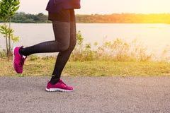 разминка женщины здоровья восхода солнца идущего ботинка бегунка дороги jog пригодности ног принципиальной схемы крупного плана с Стоковое фото RF