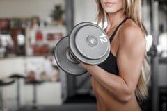 Разминка женщины с гантелью в спортзале Стоковая Фотография
