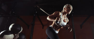 Разминка женщины фитнеса на TRX в спортзале стоковая фотография