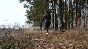 Разминка фитнеса outdoors Женщина спорта бежать через древесины