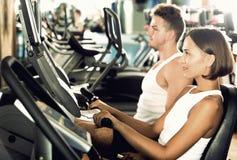 Разминка человека и женщины используя задействовать cardio машины Стоковое Фото
