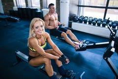 Разминка человека и женщины на имитаторе тренировки стоковая фотография rf