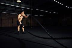 Разминка человека фитнеса с сражением ropes на спортзале тело приспособленное учебным упражнени в клубе торс стоковые фото