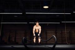 Разминка человека фитнеса с сражением ropes на спортзале тело приспособленное учебным упражнени в клубе торс стоковое фото