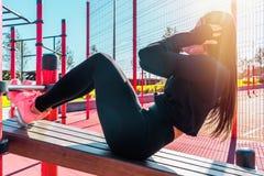 Разминка abs женщины практикуя и работать outdoors в городской среде стоковые изображения