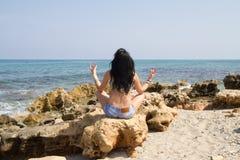Размышлять женщины усаженный в представление лотоса йоги на пляже Стоковая Фотография RF
