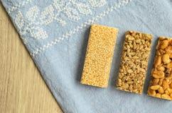 3 разного вида баров gozinaki с семенами подсолнуха, арахисами и семенами сезама на голубой предпосылке скатерти с embroid Стоковые Фотографии RF