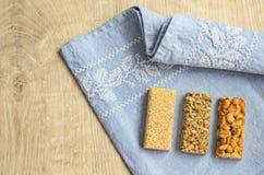 3 разного вида баров gozinaki с семенами подсолнуха, арахисами и семенами сезама на голубой предпосылке скатерти с embroid Стоковое Фото