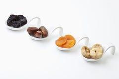 Разнообразие высушенных плодоовощей в ложке на белой предпосылке Стоковые Фото