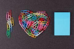 Разнообразие зажимов цвета бумажных аранжировало в форме сердца Стоковая Фотография