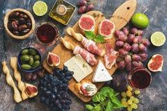 Разнообразие закуски, ветчина, виноградины, вино, сыр с прессформой, смоквами, базиликом, оливками на деревенской предпосылке Взг Стоковое Изображение