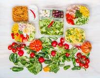Разнообразие здоровых салатов в коробках для завтрака с предпосылкой ингридиентов белой деревянной стоковые изображения