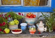 Разнообразие керамических блюд на деревянном столе на солнечный день внешний Стоковые Изображения RF