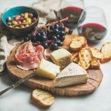 Разнообразие красного вина и закуски на деревянной доске стоковые фотографии rf