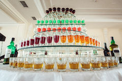 Разнообразие красочных зеленых желтых и красных съемок спирта в малых стеклах стоя в строке на стеклянной стойке Стоковые Изображения