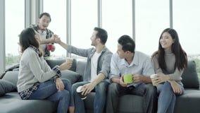 Разнообразие молодые люди собирает команду держа кофейные чашки и обсуждая что-то с улыбкой пока сидящ на кресле на офисе сток-видео