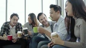 Разнообразие молодые люди собирает команду держа кофейные чашки и обсуждая что-то с улыбкой пока сидящ на кресле на офисе акции видеоматериалы