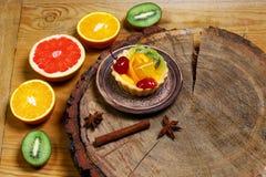 Разнообразие плодоовощей грейпфрута, апельсинов, кивиа, лимона, мяты, торта, сладостного десерта плодоовощ на плите на деревянной Стоковая Фотография RF
