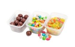 Разнообразие 3 различных конфет в малых пластмасовых контейнерах Стоковое фото RF