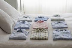Разнообразие рубашек на кровати стоковая фотография rf