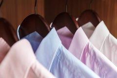 Разнообразие рубашек ` s людей на деревянные вешалки Стоковое фото RF