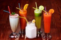 Разнообразие свежих здоровых Smoothies и коктеилей Paleo в цветах радуги на деревянной предпосылке, партии пляжа стоковое изображение rf