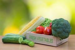 Разнообразие свежих овощей в деревянной коробке на деревянной таблице Стоковые Фотографии RF