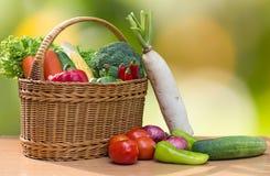 Разнообразие свежих овощей в корзине на деревянной таблице Стоковая Фотография