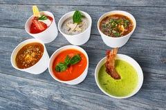 Разнообразие супов от различных кухонь на голубой древесине Стоковая Фотография RF