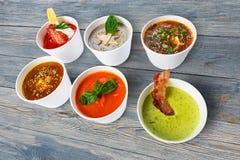 Разнообразие супов от различных кухонь на голубой древесине Стоковая Фотография