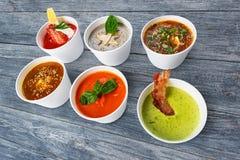 Разнообразие супов от различных кухонь на голубой древесине Стоковое Изображение RF